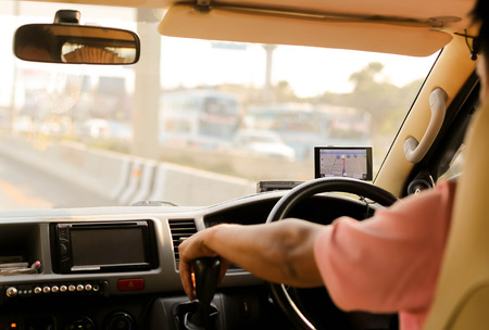 Man driving a car with navigation device on road trip 스톡 콘텐츠