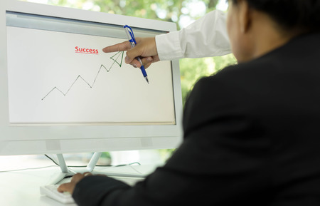 demonstrated: Business people look at graphs and charts being demonstrated on the screen of computer Stock Photo