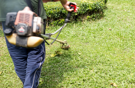 Gardener mowing the grass with petrol weed trimmer
