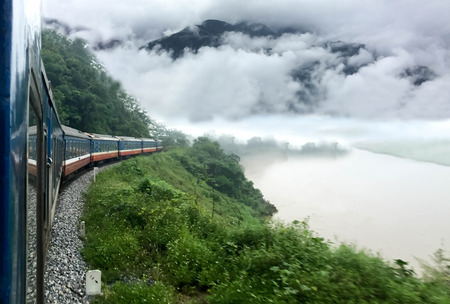 schneeberg: Train passing a beautiful fog mountains and  river view from the window Stock Photo