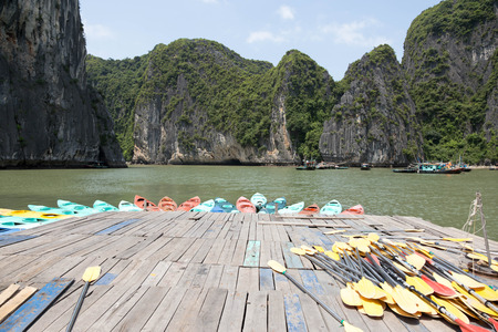 Colorful kayaks on the sea in Ha long bay Vietnam with tourist boat