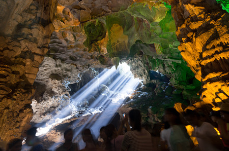 Sunbeam through ceiling hole with unidentified group of tourist in Dau Go cave Ha long Bay Vietnam