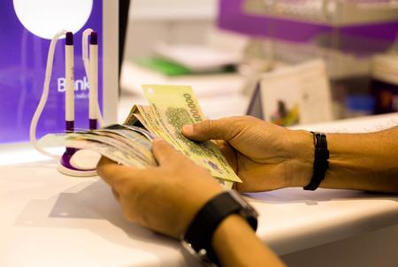Man hand with Vietnam money in cash department in Bank office