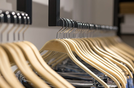 Wooden clothes hang on a shelf in a clothes store