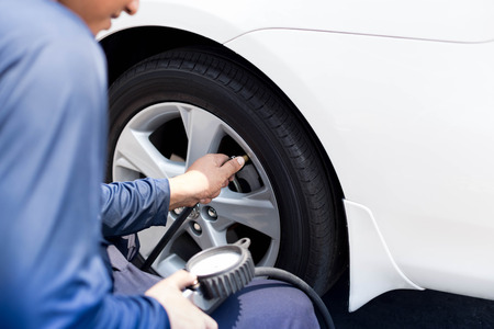 air pressure: Man checking tire air pressure with gauge