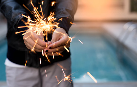Asian girl playing sparkler by swimming pool and sunset light