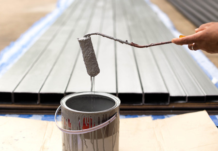 Worker dripping paint with paintroller on construction site Stock Photo