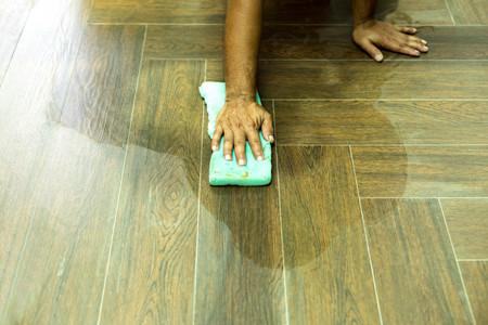 Worker cleaning floor tile after grouting tiles with sponge in construction site Standard-Bild