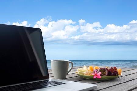 選択したフォーカス ミックス果物や花、ラップトップ木製のテーブル トップのオーシャン ビューのコーヒー ・ マグ