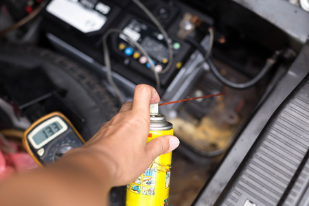 Mechanic holding aerosol cans spray oil for battery replacement in garage