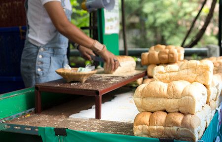 cereals holding hands: Pile of bread rolls with woman slicing in background in country style