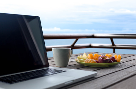 Selected focus mixes fruits plate and computer laptop with coffee mug on wooden table top ocean view Archivio Fotografico