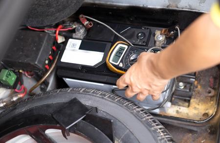 Meccanico che controlla un livello di batteria per auto con voltmetro in garage