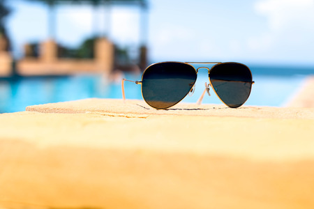 Sunglasses lying next to swimming pool with blue ocean background