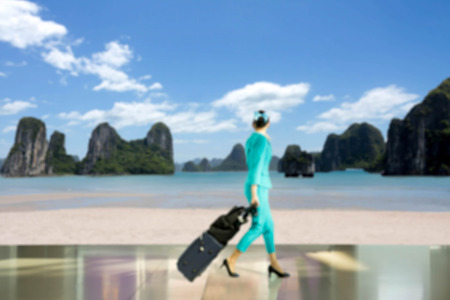 aircrew: Blurred concept travel vacation concept woman flight attendant walking with suitcase look at the island beach Stock Photo