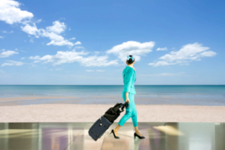 aircrew: Blurred concept travel vacation woman flight attendant walking with suitcase look at  beach with blue sky