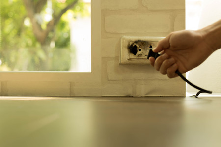 Selected focus on socket, Hand removing plug from an over heated socket in the house Stock Photo