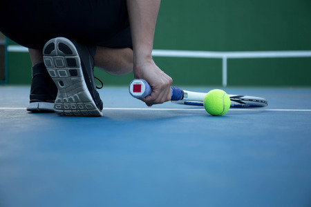 Man pick up tennis racket with tennis balls on the side in blue court