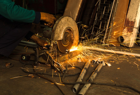 Worker use Electric grinder cutting metal with sparkle light in workshop