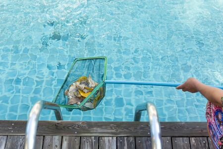 skim: Woman cleaning swimming pool of fall leaves with cleaning net in the morning Stock Photo