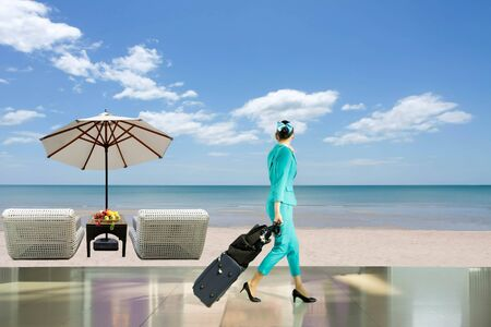 Travel vacation concept woman flight attendant with suitcase and beach chair with fresh fruit and umbrella on the beach