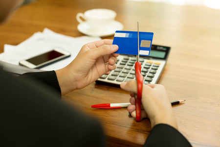 indebted: Concept bad finance woman is cutting credit card with scissors on her desk