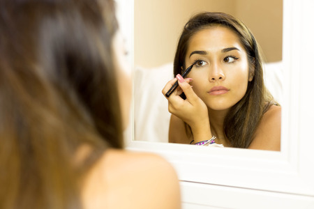 ceremonial make up: Reflective mixed race young woman with brush eye liner on with looking in the mirror Stock Photo
