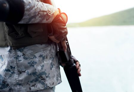 Selected focus Navy hand holding rifle standing on guard in sunlight with ocean in background