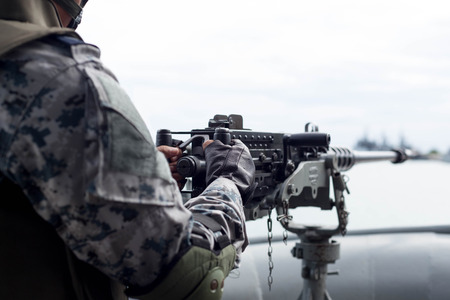 navy ship: Selected focus Navy soldier hand on machine gun on navy ship