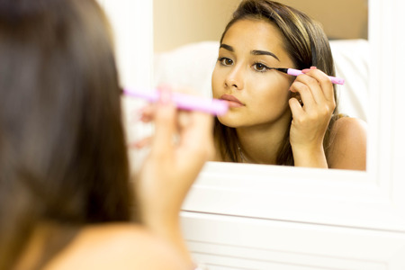 Reflective mixed race young woman with brush eye liner on with looking in the mirror Standard-Bild