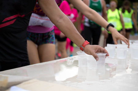 Marathon runner hand reaching pick up glass of water on the table