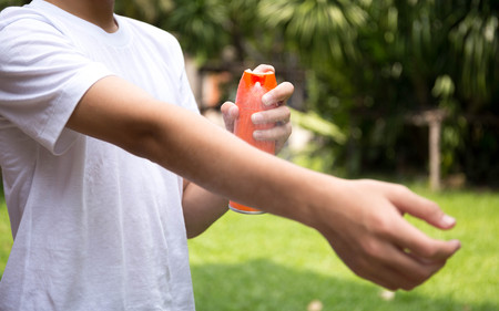 toxic substance: Young boy spraying insect repellents on skin in the garden with spray bottle Stock Photo