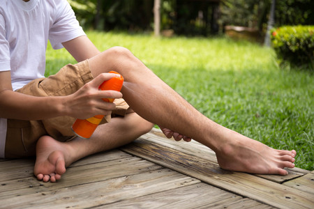 spaying: Young boy spraying insect repellents on his leg in the garden with spray bottle