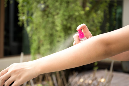 Woman spraying insect repellents on skin in the garden with spray bottle
