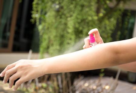 스프레이 병이있는 정원에서 피부에 곤충 기피제를 살포하는 여자