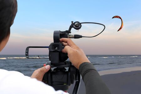 Man recording a kite surfer on the beach  in Thailand