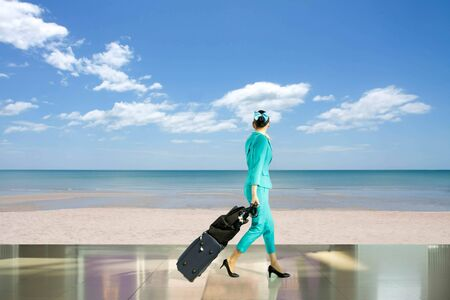 Travel vacation concept woman flight attendant walking with suitcase look at  beach with blue sky