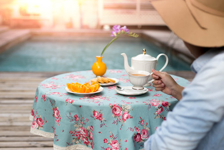 Young woman with hat drinking tea with biscuit and orange fruit next to swimming pool in light flare
