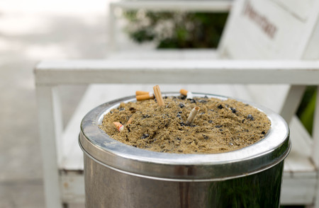 Cigarette butt , cigarette on Ashtray with sand and cigarette stubs outdoors