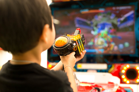 Children play shooting gun in game vending machine at playground