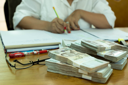 pile of money: Accounting Business woman writing with pen in notebook with pile money on the table