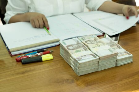 bank note: Business accountant working with documents with pile of Thai money bank note on table