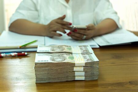 account executive: Business woman working on calculating with  pile of Thai money  bank note on the table