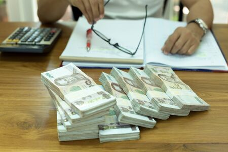 conscience: Financial concept Businessman holding glasses with pile of Thai money and notebook and calculator on the table