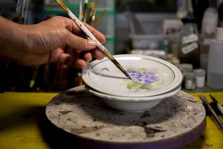 Asian woman hand painting ceramic plate in the classroom