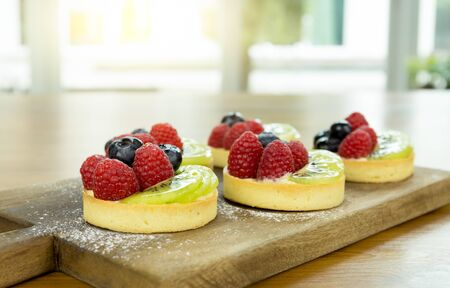 fruit tart: Fresh homemade fruit tart with berries and kiwi and icing on wooden board Stock Photo