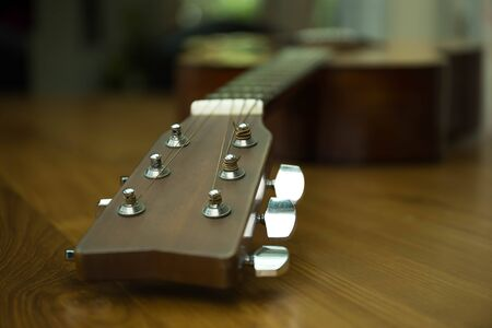 Headstock of accoustic guitar on wooden table