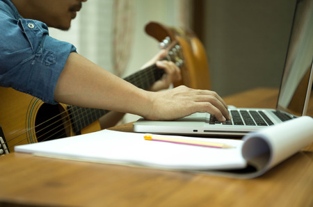 Man practicing play the guitar with laptop at home