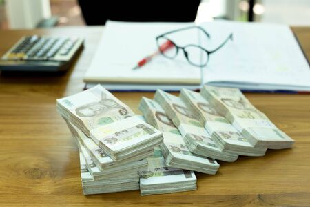 money stack: Pile of Thai money with glasses and notebook on wood table financial concept