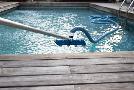 Cleaning swimming pool with vacuum tube cleaner early in the morning